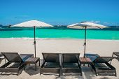 Beach Umbrellas And Loungers On Perfect White Beach