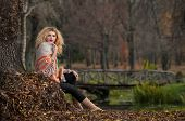 Beautiful woman posing in park during autumn season. Blonde girl wearing green blouse and big shawl