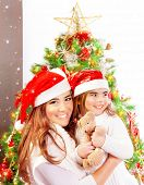 Mother with daughter celebrate Christmas, pretty woman with baby girl near Xmas tree isolated on whi