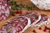 salami with walnuts and thyme bread on a wooden board