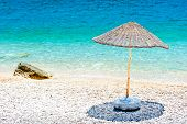 Wicker Parasol On The Beach At The Water's Edge