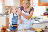 Family home baking - Mother and daughter baking cookies together at home
