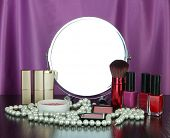 Round table mirror with cosmetics and chaplet on table on fabric background