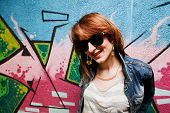 Stylish fashionable girl in jeans jacket portrait against colorful graffiti wall. Fashion, trends, subculture.