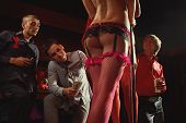 stock photo of panty-hose  - View of three men offering money to strippers on stage - JPG