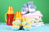 Composition with crocheted booties for baby, clothes and other things on color background