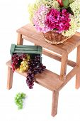 Wicker basket with flowers and fruits in wooden box,  on small wooden ladder, isolated on white