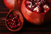 Ripe pomegranate seed in wooden spoon on bamboo mat background