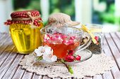 Assortment of herbs,tea and honey in glass jars and cup of hot drink on wooden table, on bright back