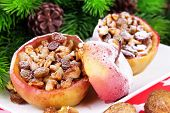 Baked Christmas apples with nuts and raisins on table close up