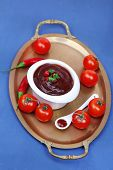 Tomato sauce in bowl on wooden table close-up