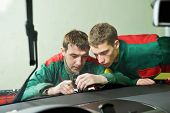 Automobile glazier repairman teaching or discussing with partner windscreen repair of a car in auto
