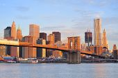Brooklyn Bridge with lower Manhattan skyline in the morning with colorful cloud over East River in N