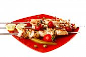 fresh grilled chicken shish kebab served with tomato cherry hot peppers on skewers over red plate is