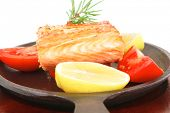 healthy diet food: hot sea grilled  red salmon fish fillet with lemon avocado and tomatoes on metal