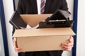 picture of disappointment  - Portrait of young businessman holding cardboard in office - JPG