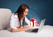 Pretty young lady sitting at desk and typing on laptop with present boxes icons