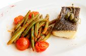 Cod fillet with runner beans and tomatoes on plate