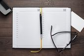 personal organizer and pen with glasses on the table