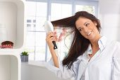 Happy young woman combing long hair by hairbrush, smiling.