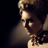 Glamour lady portrait. Beautiful model girl with perfect fashion makeup and hairstyle. Trendy accessories. Jewellery. Jewelry. Hairdo. Over Dark Background
