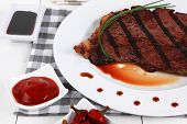 fresh rich juicy grilled beef meat steak fillet with marks on white plate over wooden table decorate