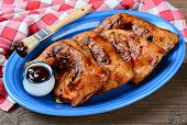 High angle shot of chicken leg quarters on a blue oval platter. The legs have been barbecued and are