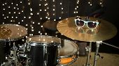 Drum set with sunglasses on cymbal in room with garland.