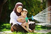 Beautiful Middle Eastern Arabic girl having baby playing with water sprinkle in garden