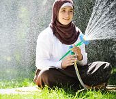 Beautiful Middle Eastern Arabic girl having happy time in summer garden with water sprinkler