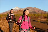 People hiking - healthy active lifestyle couple. Hikers walking in beautiful mountain nature landsca