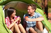 Camping couple drinking water in tent smiling happy outdoors in forest enjoying sun at looking at view. Happy multiracial couple relaxing after outdoor activity hiking. Asian woman, Caucasian man.