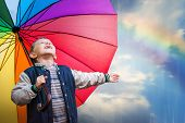 stock photo of rainy day  - Happy boy portrait with bright rainbow umbrella - JPG