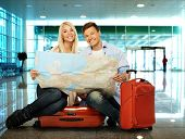 Young couple with map sitting on suitcases in airport