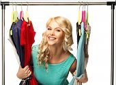 Smiling blond woman among  clothes on a rack