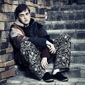 Sad young fashion man sitting on the steps