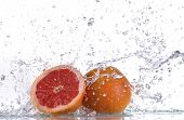 Grapefruit with water splash isolated on white