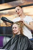 Female hairdresser drying hair with blow dryer of woman client at beauty parlour after highlighting