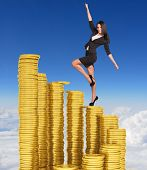 Businesswoman climbing stairs of gold coins