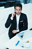 Attractive rich man in suit talking on mobile phone looking to the camera