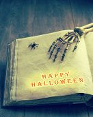 Happy Halloween with a skeleton hand over the pages of an old tomb