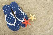 Flip flops on sea sand background