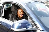 African Woman Smiling As She Drives Her Car