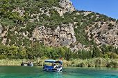 stock photo of dalyan  - Tourist boats by the historic Kaunian rock tombs in Dalyan - JPG