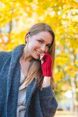 Young woman dressed in warm woollen jersey and mittens standing looking down at the camera with a a smile in a colorful autumn garden