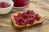 slice of fresh banana bread with walnut and cranberry sauce on a grunge cutting board
