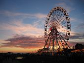 stock photo of ferris-wheel  - Ferris Wheel at sunset with red clouds in background and lights on wheel - JPG
