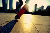 stock photo of skateboarding  - woman skateboarder legs skateboarding at sunrise city - JPG