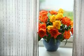 Beautiful, colorful and fresh bouquet of orange and yellow roses in a ceramic pot, on a window sill