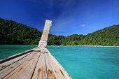 Long Tail Wooden Boat Sailing On Crystal Sea